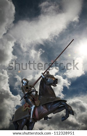 Knight on horseback, against clouds, with lance - stock photo