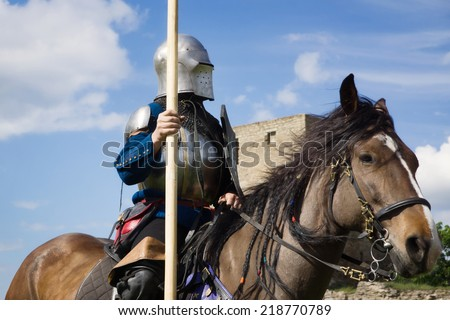 Knight on horseback over blue sky background  - stock photo