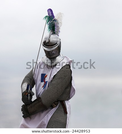 Knight with a sword in mail shirt, armament and helmet (copy space) - stock photo