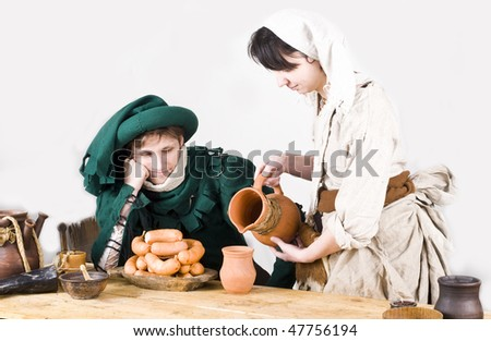 knight with beer and sausage in tavern - stock photo