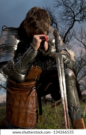 Knight with sword. Praying - stock photo