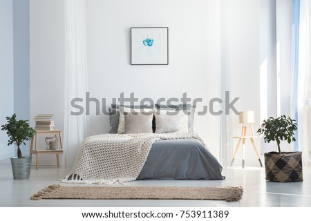 Knit blanket on king-size bed in natural warm bedroom of modern apartment in soft gray and blue colors