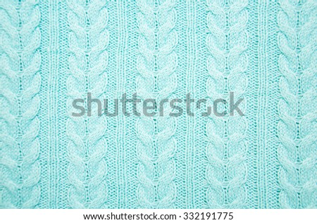 knit texture of blue wool knitted fabric with cable pattern as background - stock photo