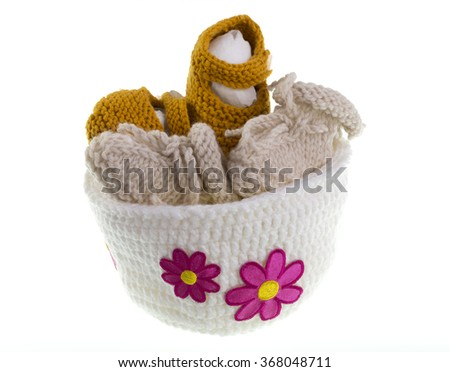 Knitted baby booties and shoes inside a hat with flowers - stock photo