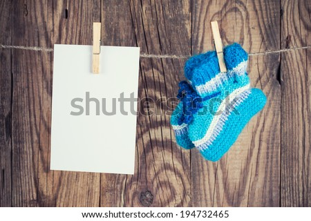 knitted baby socks and blank note hanging on clothesline against wooden background - stock photo