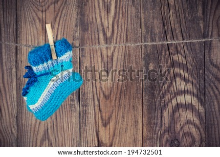 knitted baby socks hanging on clothesline against wooden background - stock photo