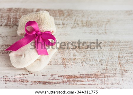 knitted baby socks with rose bow on the wooden surface - stock photo