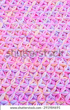 Knitted background with threads of pink in the shape of flowers - stock photo
