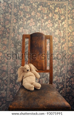 knitted bunny sitting on an old chair background - stock photo
