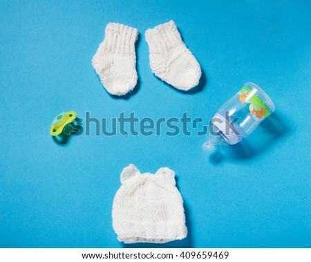 Knitted by hands wool white hat and socks for the newborn. Winter hand made clothing for the child on blue paper background. Hobbies for Women: knitting. - stock photo