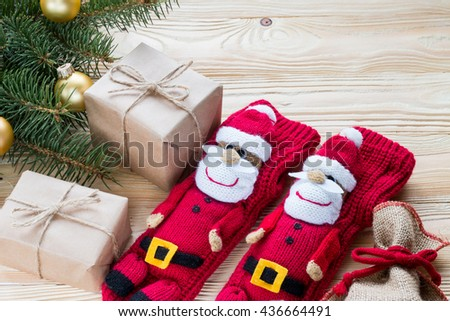 knitted Christmas Stockings as Santa Claus, christmas gifts packaged in kraft paper,  jute rope constricted  on wooden table with Christmas tree . top view, free space for text - stock photo