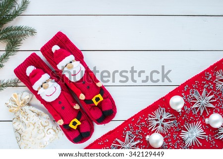 knitted Christmas Stockings as Santa Claus on white painted wood background with Christmas tree and decorations. Red tablecloth with silver Christmas tree decorations. Top view, free space for text. - stock photo