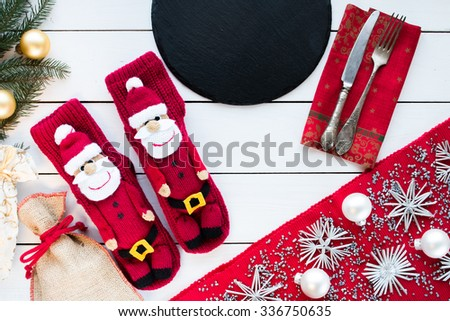 knitted Christmas Stockings as Santa's on white painted wood background with Christmas tree and decorations. Red tablecloth with silver decoration,black pan, silver cutlery. Top view - stock photo