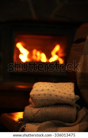 Knitted clothes on chair on fireplace background