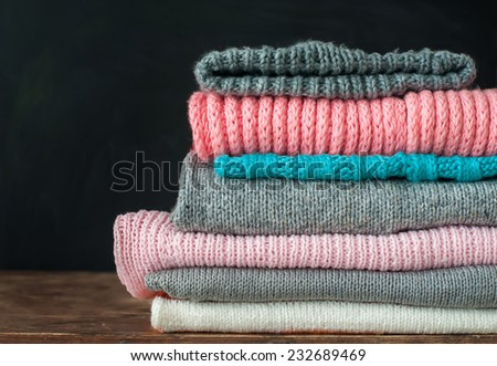 Knitted Color Clothes in stack on Black Background, home sweet things - stock photo