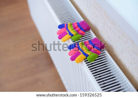 Knitted gloves drying on heating radiator - stock photo
