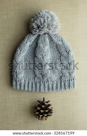 Knitted gray hat with pompom and pine cones. Winter soon or Knitted hat - stock photo