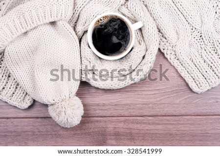 Knitted handmade wool scarf and hat. Autumn or winter womans clothes. Needlework clothes. Hot coffee cup on wooden background. Top view  - stock photo