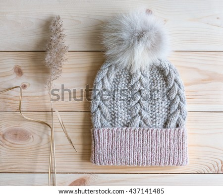 knitted hat and dried plant on a wooden background - stock photo