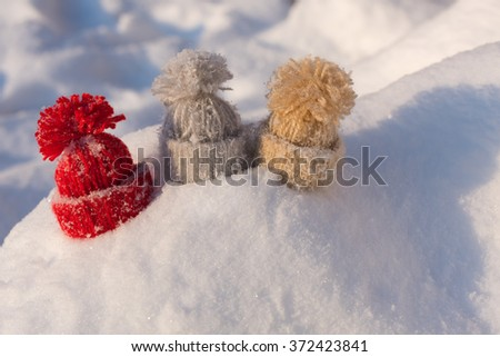 Knitted hats on the snow. Winter concept / background - stock photo