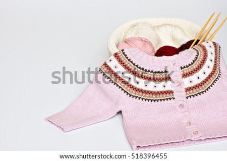 Knitted jacket for the baby with balls of wool and knitting needles isolated on white background/ Knitting / Hobby/