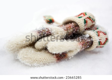 Knitted mittens lost by somebody on the snow - stock photo
