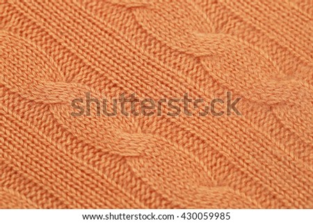 Knitted Norwegian diagonal pattern with front and reverse loop braids from orange-colored cashmere yarn,  close up - stock photo