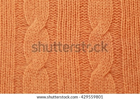 Knitted Norwegian pattern with front and reverse loop braids from peach-colored cashmere yarn, fashion background, close up - stock photo