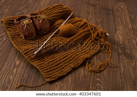 Knitted piece  and knitted kids shoes are on the wood table - stock photo