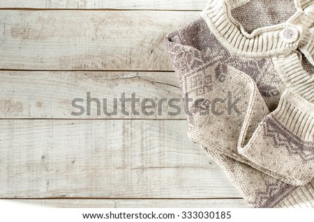 knitted pullover on wooden boards with copy space for text.
