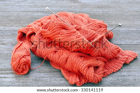 knitted scarf from cotton yarn with knitting needles and a ball on wooden background - stock photo