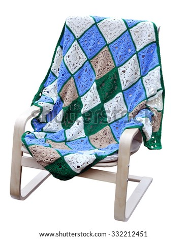 Knitted squares of a blanket lying on a wooden chair. - stock photo