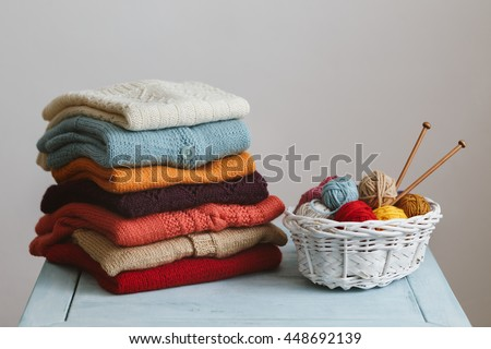 Knitted sweaters with knitting needles and wool - stock photo