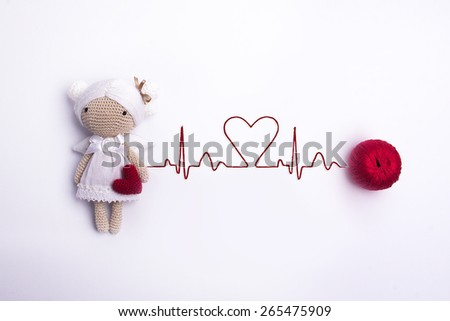 knitted toy girl of yarn in a white dress with white and brown hair with red heart in hand, cardiogram - stock photo