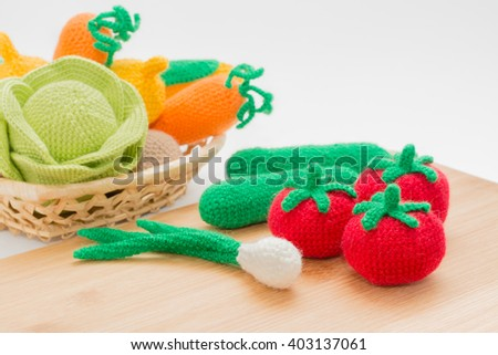 Knitted vegetables on a cutting board in a wicker basket