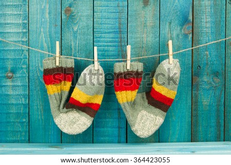 Knitted wool colorful socks on turquoise wooden background
