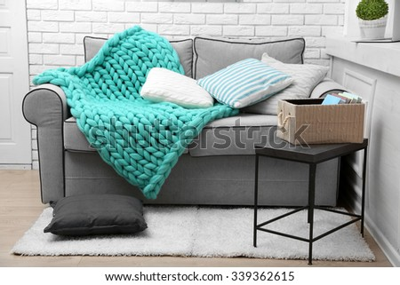 Knitted woolen blanket on sofa, on home interior background - stock photo