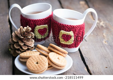 Knitted woolen cups on a wooden table  - stock photo