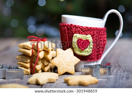 Knitted woolen cups on a wooden table, christmas - stock photo