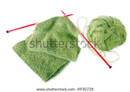 Knitting a green fluffy woollen scarf, with red knitting needles.  Isolated on white with shadow. - stock photo