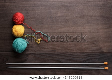 knitting needles and colorful ball of threads on wooden background - stock photo