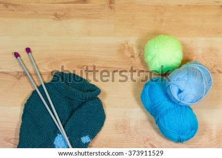 Knitting needles, ball of yarn and knitted sweater are lying on the wooden desk.  - stock photo