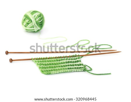 Knitting pattern of green yarn on wooden needles isolated on a white background