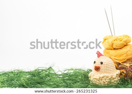 knitting toy chicken on a background of thread grass - stock photo