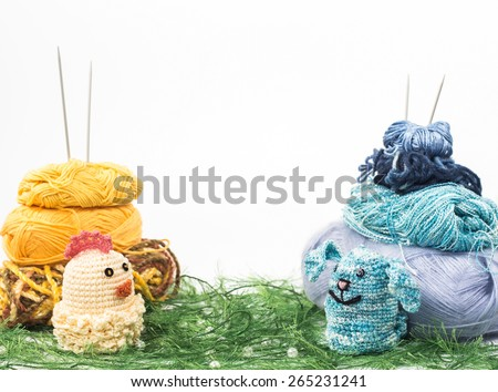 knitting toy rabbit and chicken on a background of thread grass - stock photo