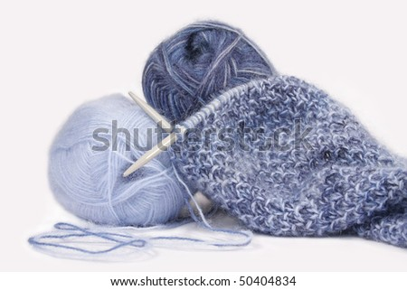 Knitting with blue fluffy wool, on knitting needles. - stock photo