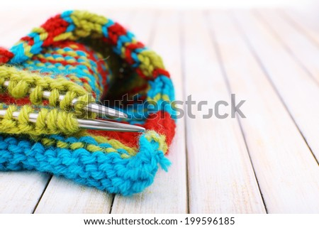Knitting with spokes on wooden background - stock photo