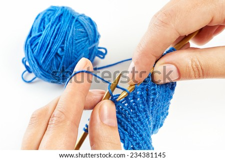 Knitting with two spokes. Blue wool and female hands. Isolated macro. - stock photo