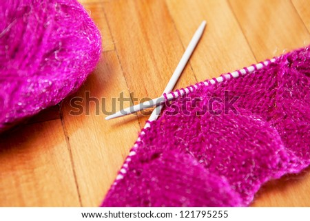 knitting wool and knitting needles on wooden background - stock photo