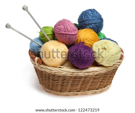 Knitting yarn balls and needles in basket on a white background - stock photo